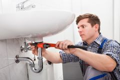 修理水槽的男性水管工画象 库存图片