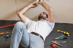 修理水槽的水管工在卫生间里 免版税库存图片