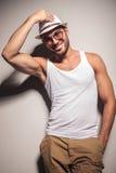 修理他的帽子的愉快的年轻时尚人 库存照片
