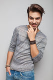修理他的胡子的微笑的年轻时尚人 免版税库存照片
