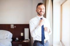 修理他的领带的拉丁商人在旅馆里 免版税库存图片
