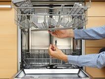修理洗碗机的杂物工 免版税库存照片