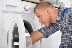 修理洗衣机的杂物工 免版税库存照片