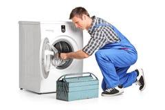 修理洗衣机的年轻水管工 库存照片