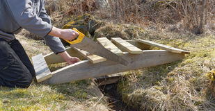 修筑一座小木弯曲的桥梁的人 库存图片