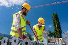 修造一个金属绞刑台的两名高效率的蓝领工装的雇员 免版税库存照片