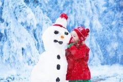 修造一个雪人的小女孩在冬天 库存照片