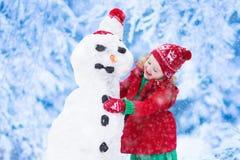 修造一个雪人的小女孩在冬天 库存图片