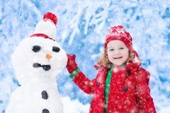 修造一个雪人的小女孩 免版税库存照片