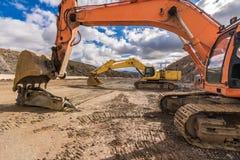 修造不同颜色不同的colorsExcavators的路修造路的挖掘机  库存图片