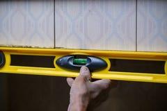 修造产业工人的用途平实检查墙壁平衡边缘到检查墙壁的水平在建筑 免版税图库摄影