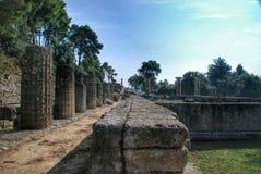 修造在古老奥林匹亚考古学站点留在希腊 图库摄影