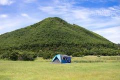 修造帐篷野营在休息的草地的旅客人并且在山附近睡觉 库存图片