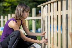 修造庭院篱芭的妇女 免版税图库摄影