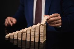 修造成功的图表或梯子在黑桌上的商人 免版税库存照片