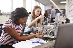 修造机器在科学机器人学方面或设计类的两位女性大学生 免版税库存照片