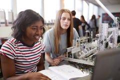 修造机器在科学机器人学方面或设计类的两位女性大学生 免版税库存图片