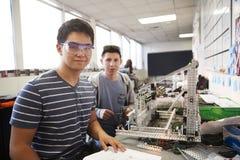 修造机器在科学机器人学方面或设计类的两位男性大学生画象  免版税库存图片