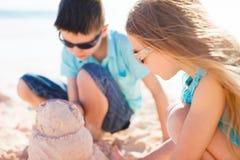 修造沙子城堡的两个孩子 库存图片