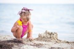 修造沙子城堡的海滩的小女孩 库存图片