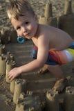 修造海滩沙子城堡的逗人喜爱的年轻男孩 免版税库存图片