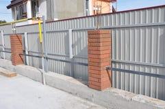 修造的金属,有钢棍框架的砖篱芭 Install操刀 免版税库存照片