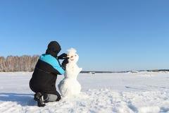 修造雪人的人 免版税库存照片