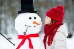 修造雪人的可爱的小女孩在美丽的冬天公园 使用在雪的逗人喜爱的孩子 免版税库存图片