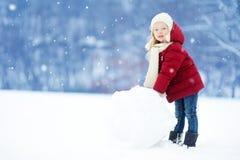 修造雪人的可爱的小女孩在美丽的冬天公园 使用在雪的逗人喜爱的孩子 库存照片