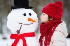 修造雪人的可爱的小女孩在美丽的冬天公园 使用在雪的逗人喜爱的孩子 图库摄影