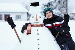 修造雪人的少年 免版税库存图片