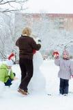修造雪人的母亲和孩子 免版税图库摄影
