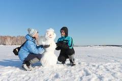 修造雪人的男人和妇女 免版税库存图片