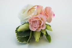 修饰与一朵桃红色玫瑰和两只婚姻的金戒指的` s钮扣眼上插的花 库存照片