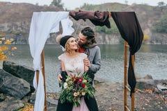 修饰嫩拥抱她美丽的新娘后边 秋天在户外土气样式的婚礼 愉快 免版税图库摄影