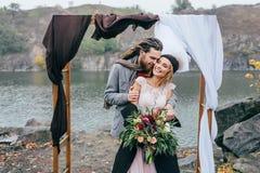 修饰嫩拥抱她美丽的新娘后边 秋天在户外土气样式的婚礼 愉快 图库摄影