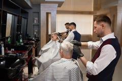 修饰客户` s理发的男性美发师在理发店 图库摄影