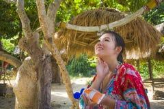 修饰年轻美丽和愉快的亚裔韩国的妇女投入太阳块保护的奶油化妆水在热带天堂海滩r 免版税库存图片