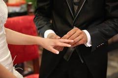 修饰把圆环放在他的在他们婚姻的da的新娘的手指上 免版税库存照片
