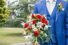 修饰拿着与蓝色衣服和白领结的婚礼花束 库存图片