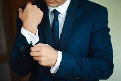 修饰早晨准备,英俊的新郎换衣服和为婚礼做准备,在深蓝套装 免版税图库摄影