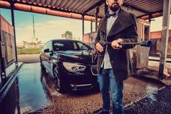 修饰的人摆在与水管在车洗涤的驻地在他的汽车附近 免版税库存图片