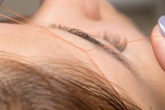 修饰眼眉穿线在美容院 库存照片