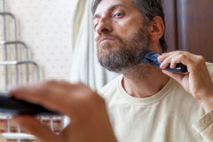修饰胡子 单独人在卫生间里剪胡子 库存图片