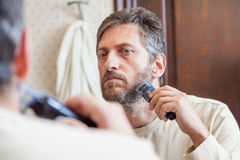 修饰胡子 单独人在卫生间里剪胡子 库存照片