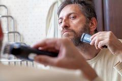 修饰胡子 单独人在卫生间里剪胡子 图库摄影