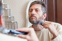 修饰胡子 单独人在卫生间里剪胡子 免版税库存照片