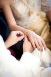 修饰他的新娘的佩带的金镯子婚礼的 免版税库存照片
