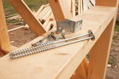 修建一个木房子的螺丝和钉子 加入的木粱 建筑工作 库存图片