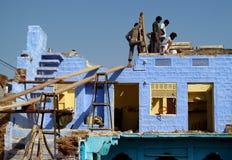 修建一个蓝色房子的印度人民 免版税图库摄影